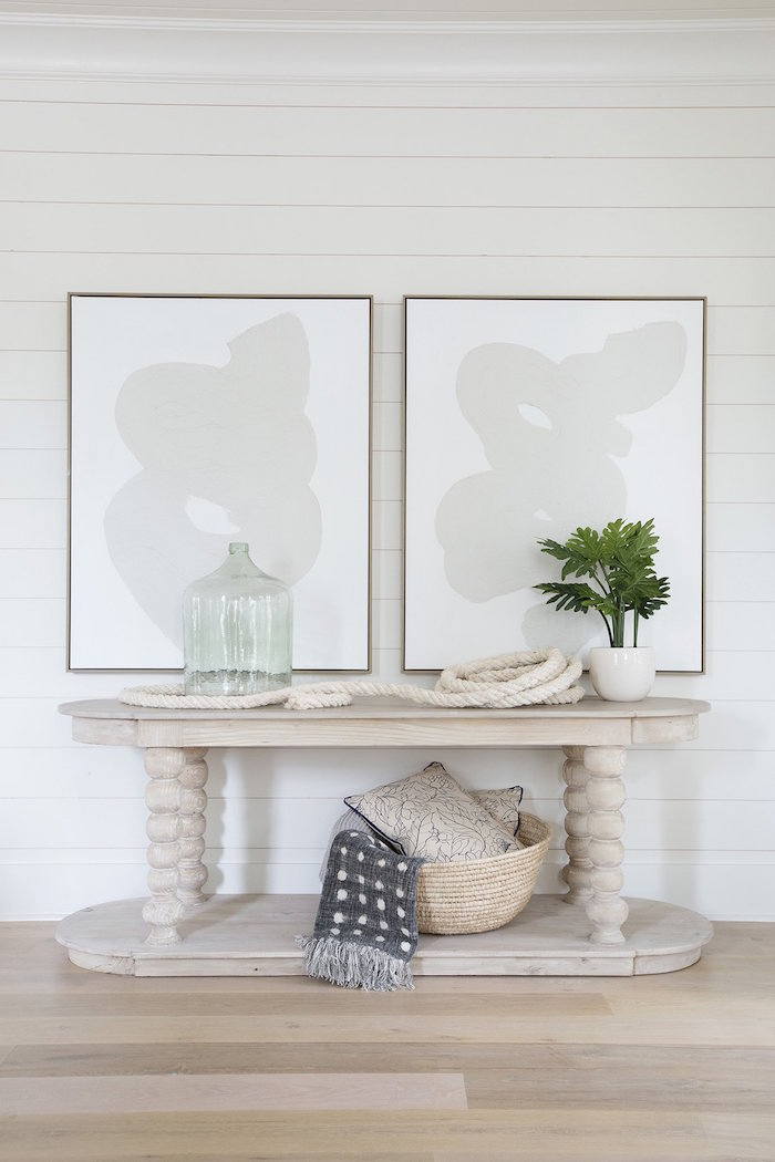 framed art on white shiplap wall above wooden table with decorations made from rope nautical decor hallway design