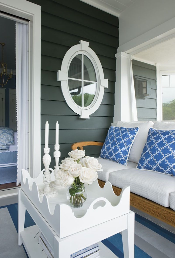 front porch with white sofa with blue throw pillows white wooden coffee table black shiplap walls beach decor