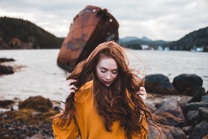ginger haired woman wearing mustard yellow sweater standing next to lake keep your hair healthy long wavy hair
