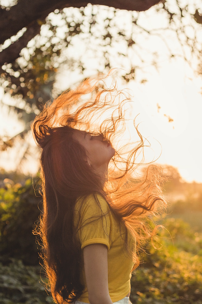 girl with long brown wavy hair flipping it wearing yellow top standing in the sun keep your hair healthy