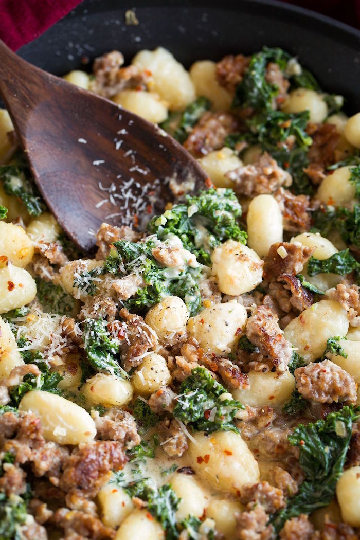 gnocchi cooked in black pan stirred with wooden spoon easy gnocchi recipe with italian sausage and kale