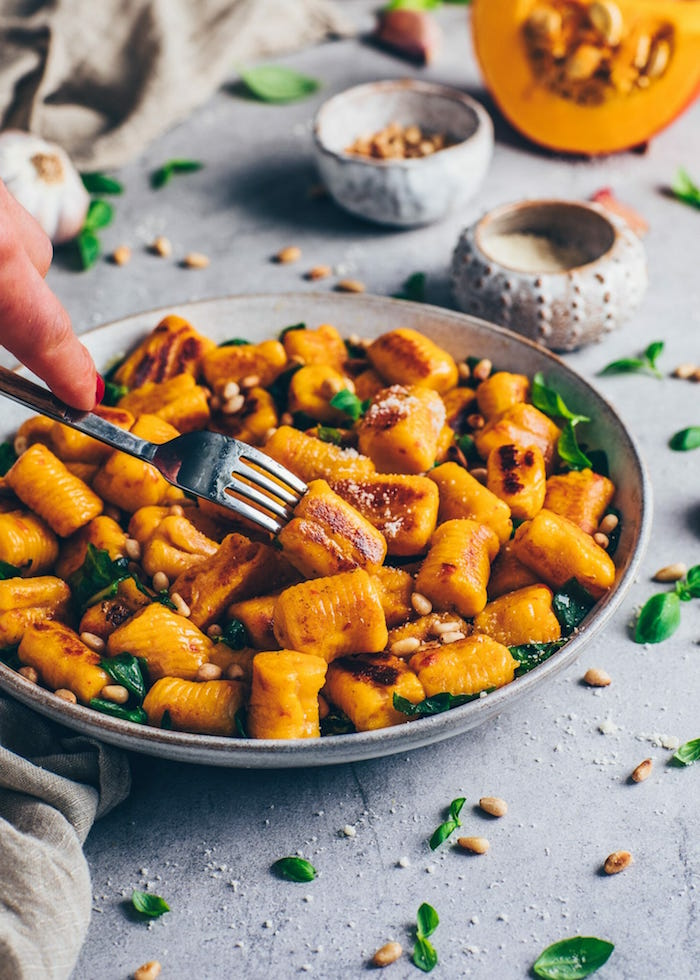 gnocchi recipe vegan potato gnocchi with fresh basil leaves and pine nuts inside gray bowl placed on gray surface