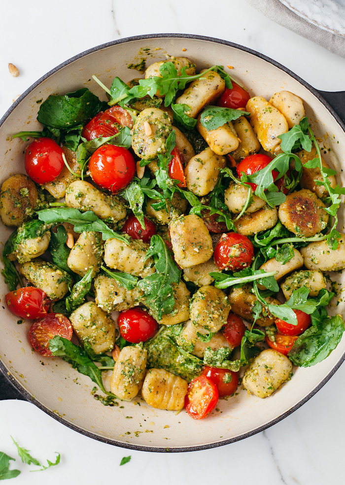 gnocchi with basil pesto fresh cherry tomatoes arugula spinach inside white pan gnocchi recipe