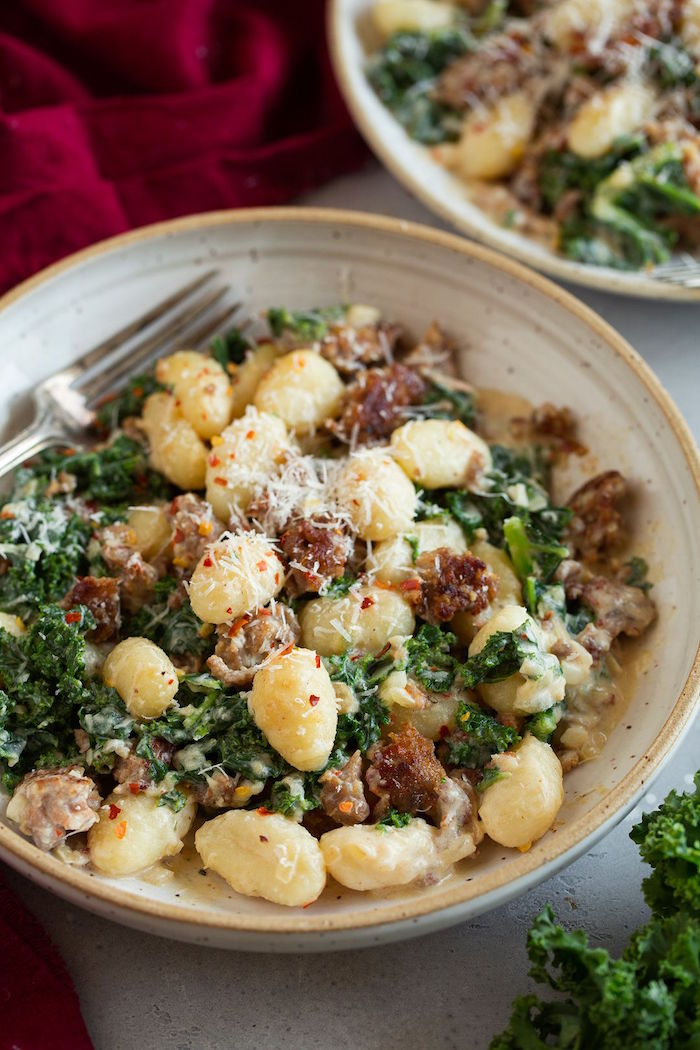 gnocchi with italian sausage and kale garnished with grated parmesan cheese easy gnocchi recipe in gray plate fork on the side