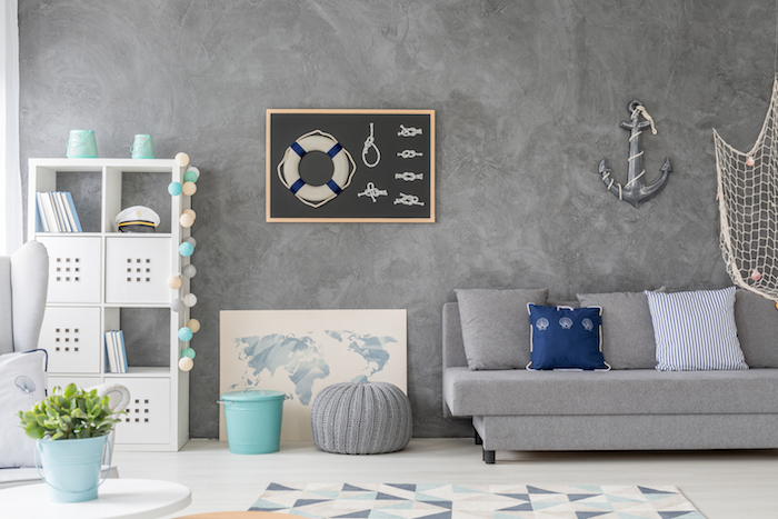 gray accent wall gray sofa with blue and white throw pillows coastal decorating ideas white bookshelf