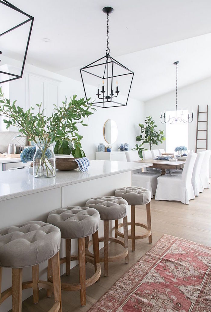 gray bar stools next to large white kitchen island coastal decor dinner table with white chairs lots of blue flower bouquets