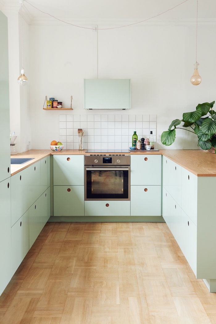 green kitchen cabinets small kitchen remodel white tiled backsplash wooden countertop and floor
