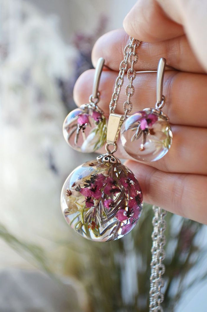 hand holding silver necklace and pair of earrings resin jewelry pink dried flowers inside blurred background