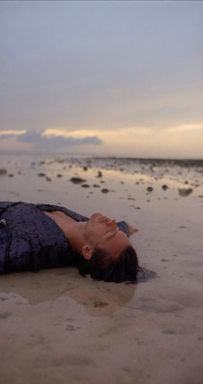 harry lying on the beach harry styles pictures wearing black sequinned shirt with closed eyes