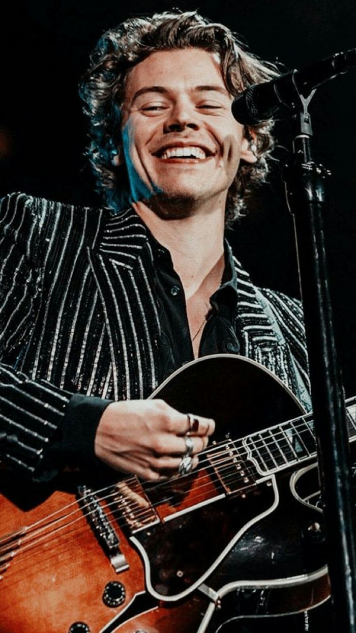 harry on stage smiling wearing black striped blazer harry styles aesthetic wallpaper playing the guitar