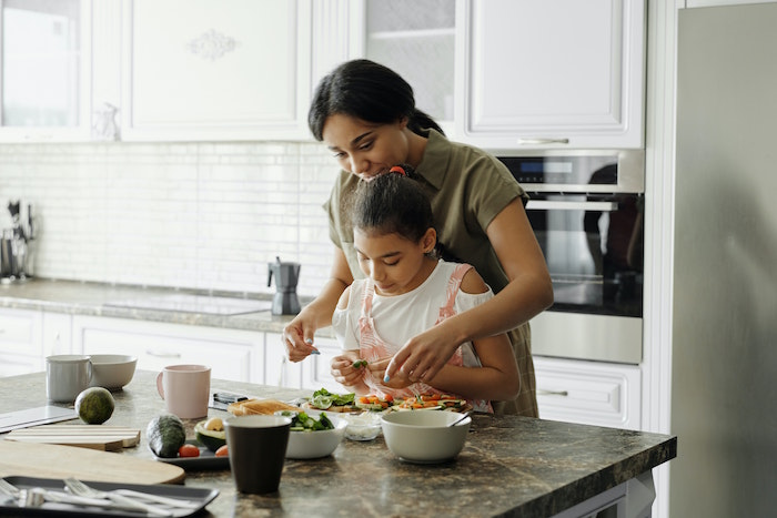 inflammatory foods mom and daughter standing next to kitchen island with granite countertop cutting up greens together
