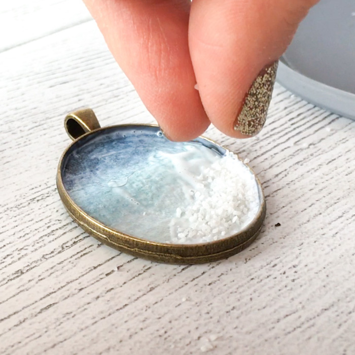jewelry making for beginners vintage bronze necklace pendant being filled with salt placed on white wooden surface