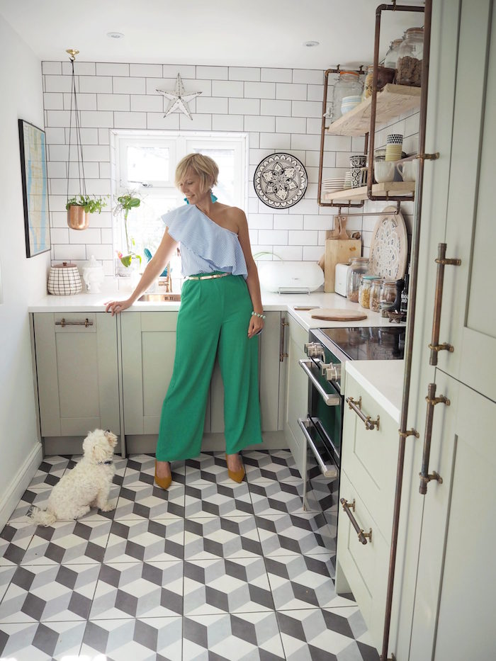 kitchen decorating ideas woman standing in kitchen with open shelving white subway tiles backsplash gray and white tiled floor
