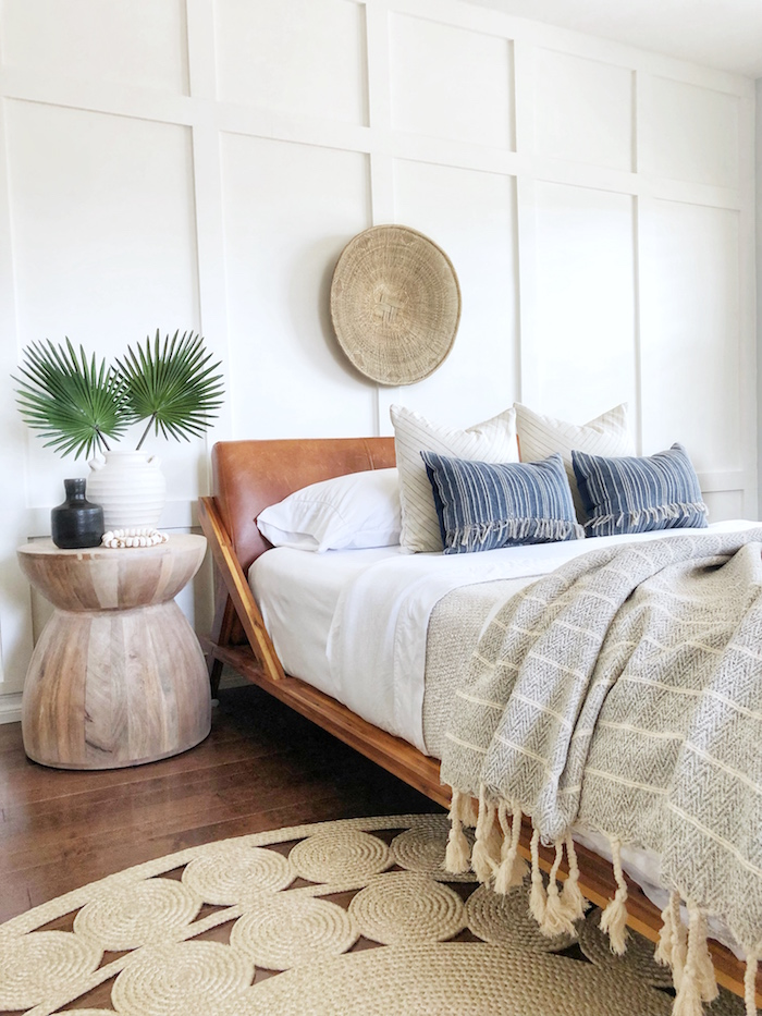 leather bed frame in brown on bed with blue and white throw pillows coastal decorating ideas white walls