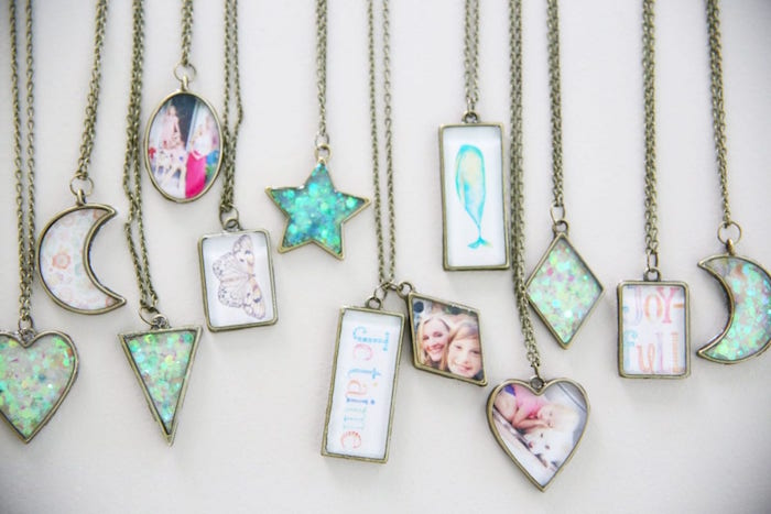 lots of different bronze necklaces in different shapes epoxy resin jewelry with photos and drawings inside placed on white surface
