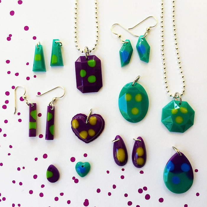 lots of different pendants and earrings in turquoise and purple with green yellow dots resin jewelry molds placed on white surface