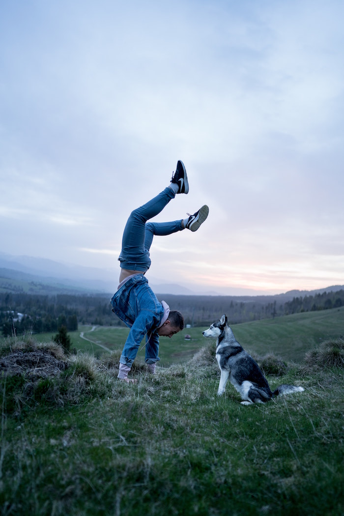 man wearing jeans pink hoodie denim jacket black sneakers doing a hand stand inflammatory foods black and white husky dog standing next to him