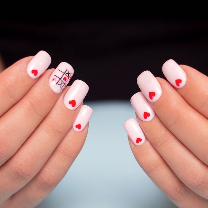 medium length squoval nails covered with white nail polish valentines day nails 2021 small red hearts on each nail tic tac toe decoration on middle finger