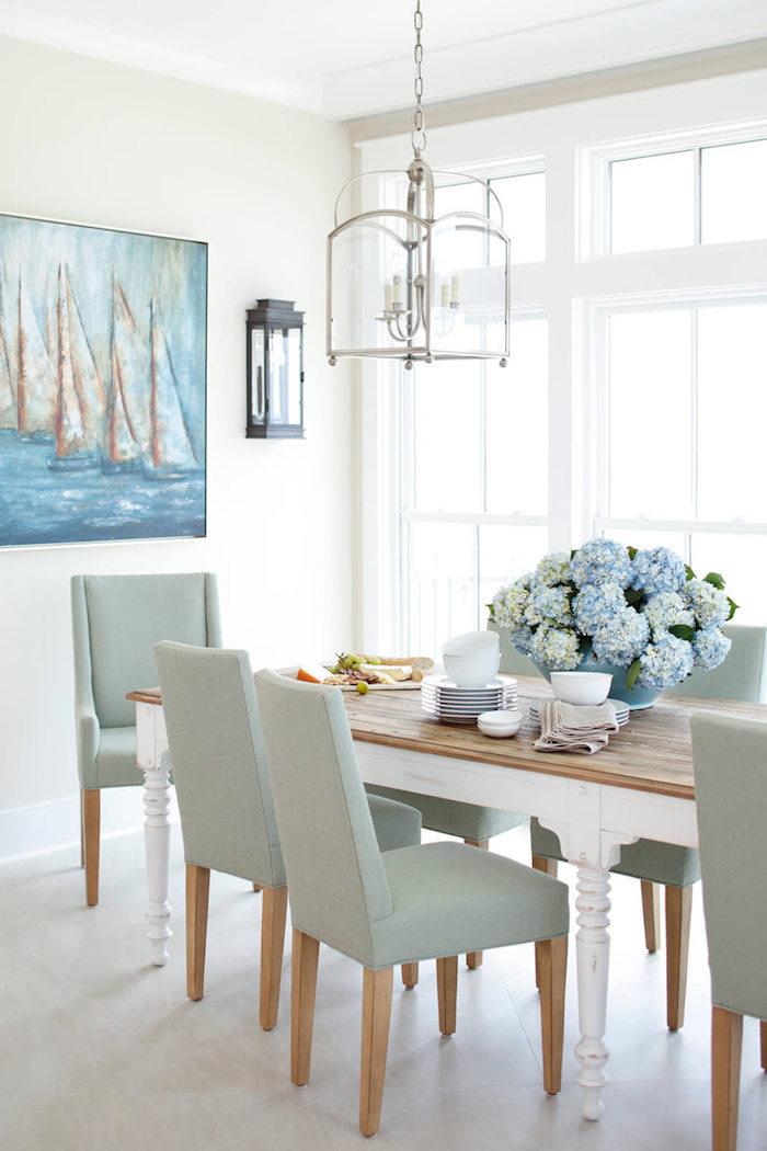 nautical decor gray chairs surrounding wooden dining table with large blue flower bouquet in the middle painting of boats in the sea on white wall