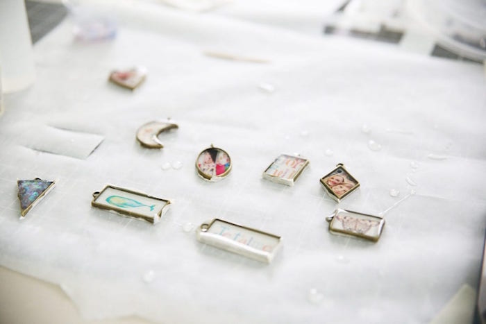 necklace pendants in different shapes arranged on white paper epoxy jewelry with photos and drawings inside