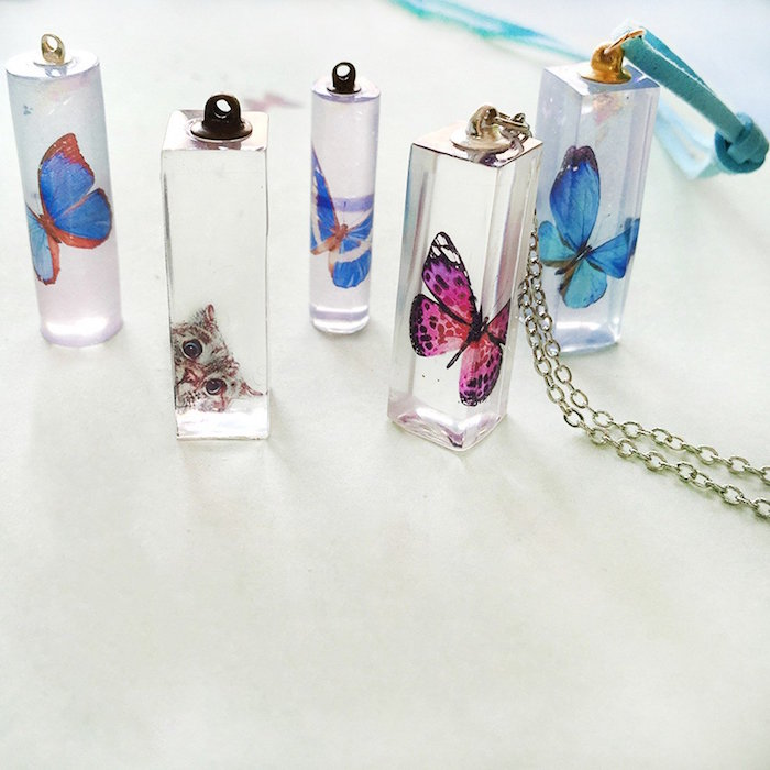 necklace pendants with paper butterflies and cat inside resin earrings in square and cilinder shapes placed on white surface