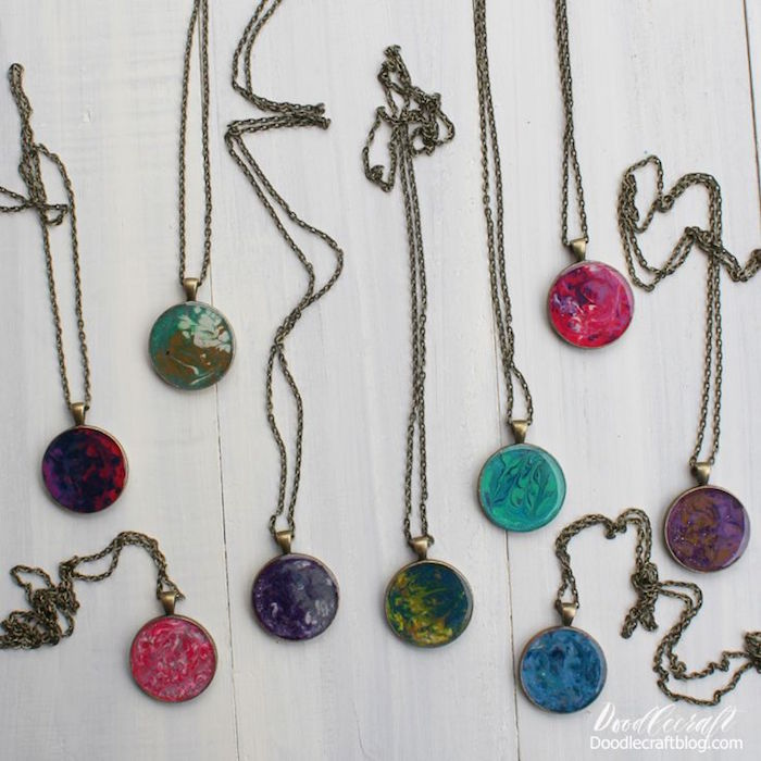 nine different marble necklace pendants making resin jewelry with vintage bronze chains arranged on white wooden surface