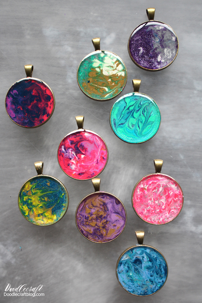 nine necklace pendants placed on marble surface all in different colors epoxy jewelry green blue red pink purple yellow