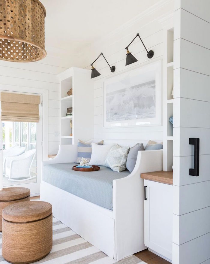 nook in the hallway with white bench with blue cushions throw pillows beach bathroom decor white shiplap walls