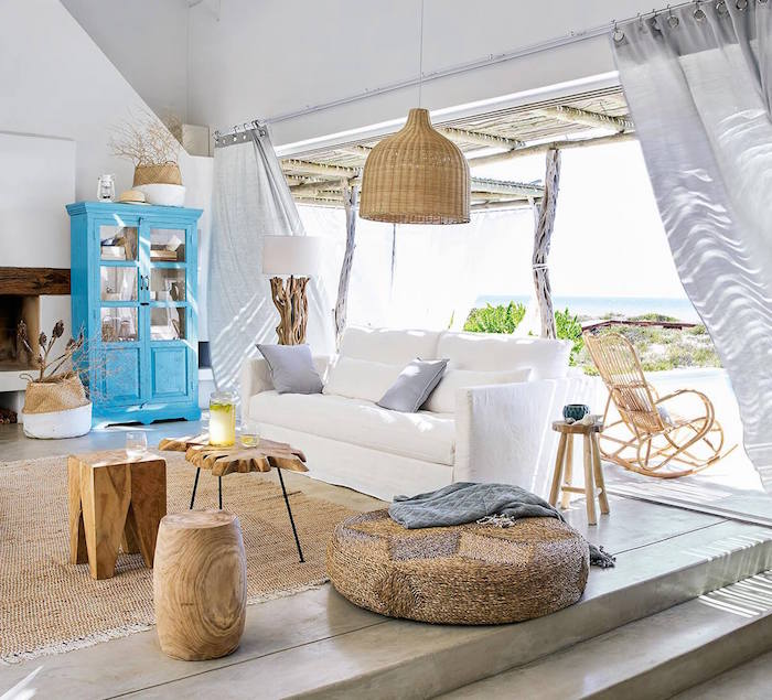 open living room with curtains coastal home decor white sofa wooden coffee tables blue vintage bookshelf