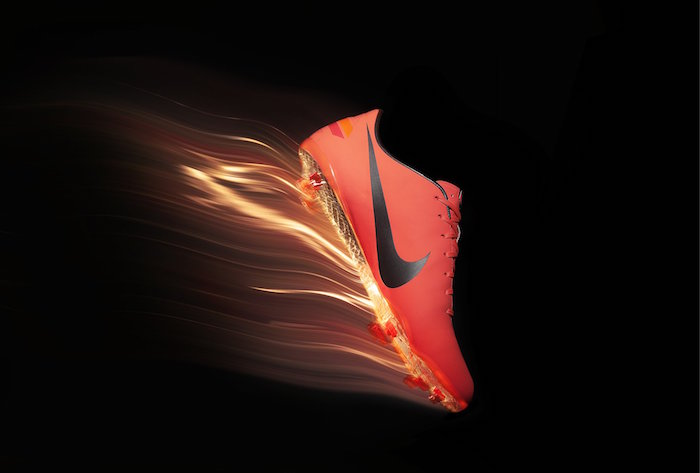 orange nike football boot with black nike logo on it cool nike wallpapers photographed on black background