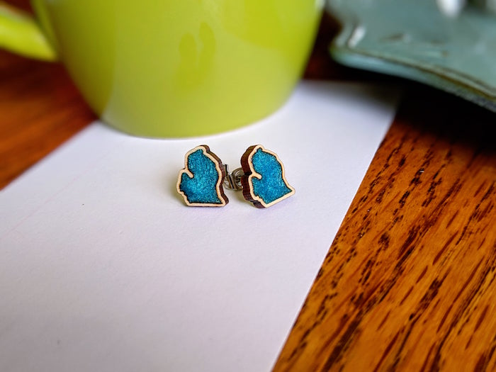 pair of earrings in gold with turquoise blue resin inside in abstract shape resin jewelry molds placed on white piece of paper on wooden surface