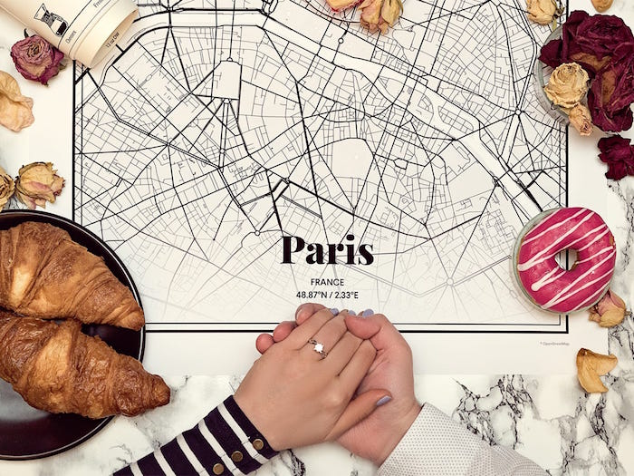 personalised map of where you first met placed on marble surface valentine's day gifts for men couple holding hands with engagement ring