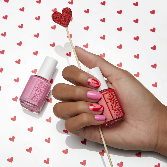 pink and red nail polish with hearts drawn on index and ring finger valentines nails short squoval nails