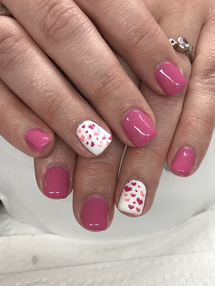 pink and white nail polish on short squoval nails valentines nails red and pink hearts drawn on ring fingers