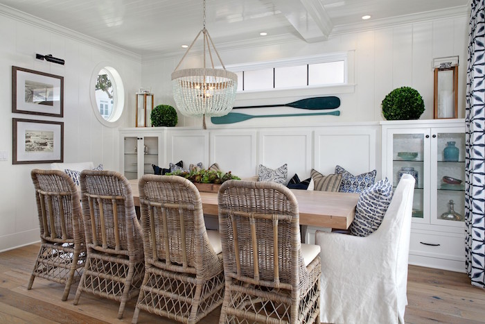 rattan chairs around wooden dining table next to bench with lots of throw pillows beach decor white walls two blue paddles hanging on the wall