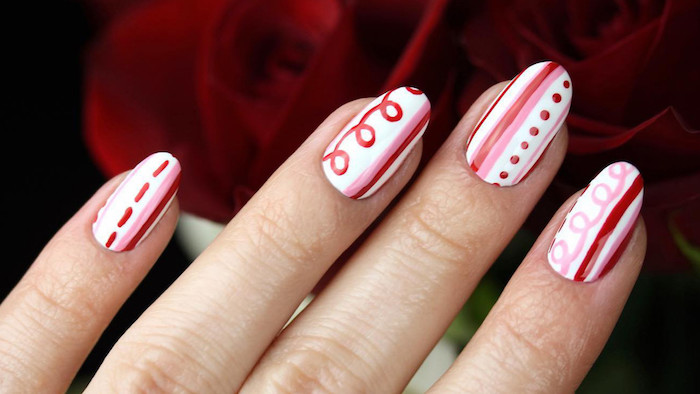 red and pink lines and dots drawn on white nail polish valentines day nails medium length almond nails