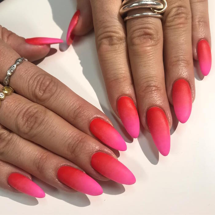 red and pink matte ombre nail polish valentine's day acrylic nails long almond nails on woman wearing silver rings