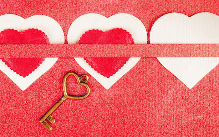 red background three white cardstock hearts tied with red ribbon valentines background gold key under them