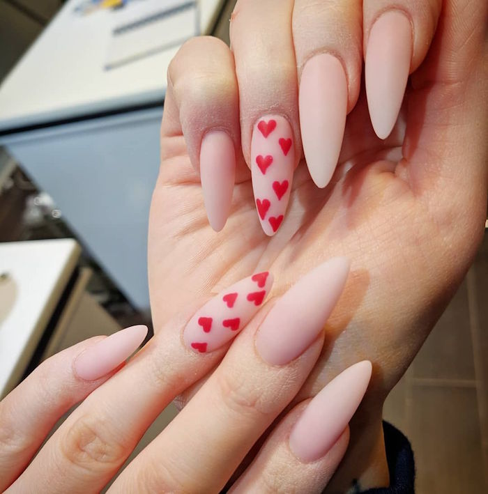 red hearts drawn on ring fingers cute nail designs beige matte nail polish on long stiletto nails