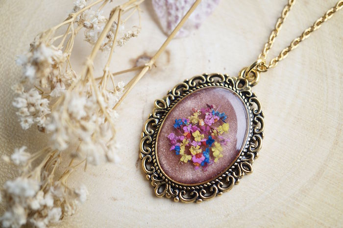 resin jewelry vintage necklace with dried flowers inside eliptical form gold necklace chain placed on white cloth next to dry flowers