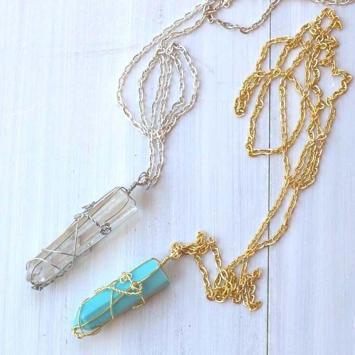 resin necklace with crystals and silver and gold chains placed on white wooden surface step by step diy tutorial