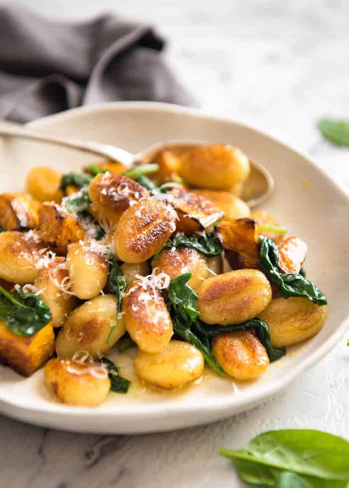 roasted pumpkin gnocchi with spinach garnished with grated parmesan cheese gnocchi recipe white plate on white wooden surface