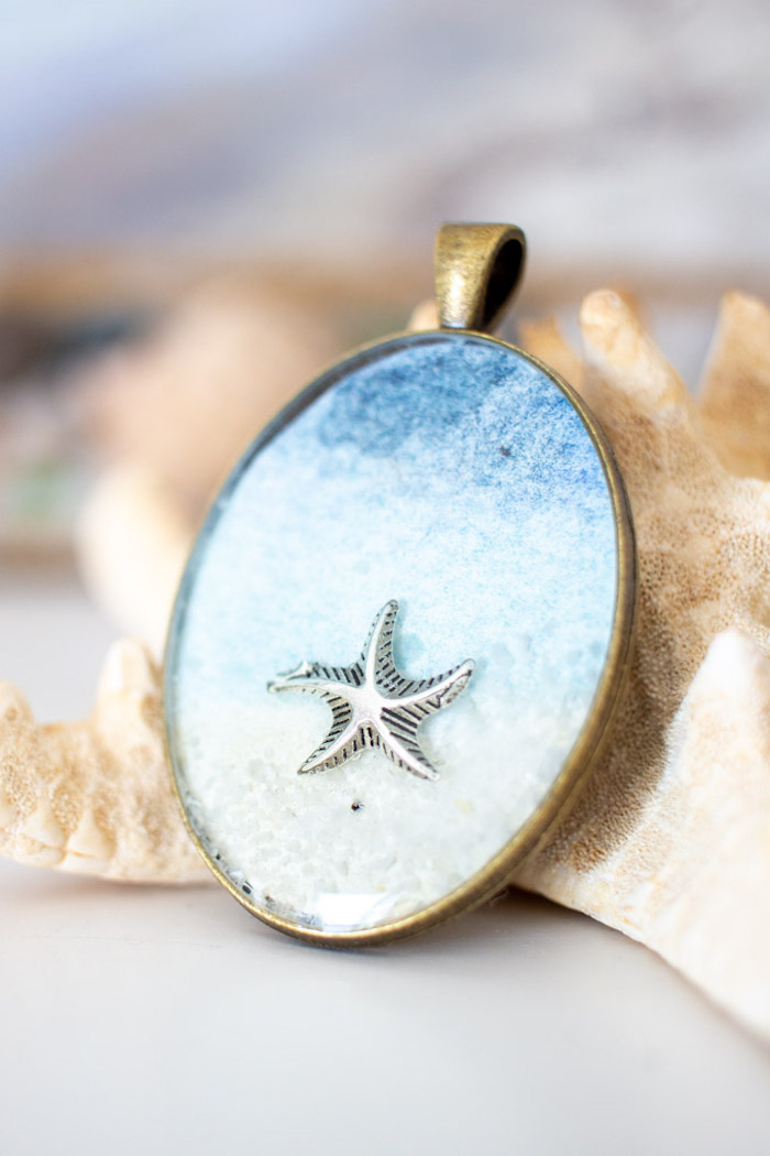 sea star placed inside bronze vintage necklace pendant with blue watercolor paper jewelry making for beginners