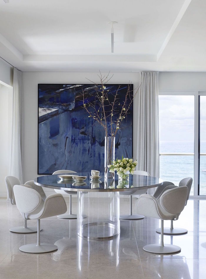 small beach house large round glass table with light gray chairs around it large abstract painting on the wall in shades of blue