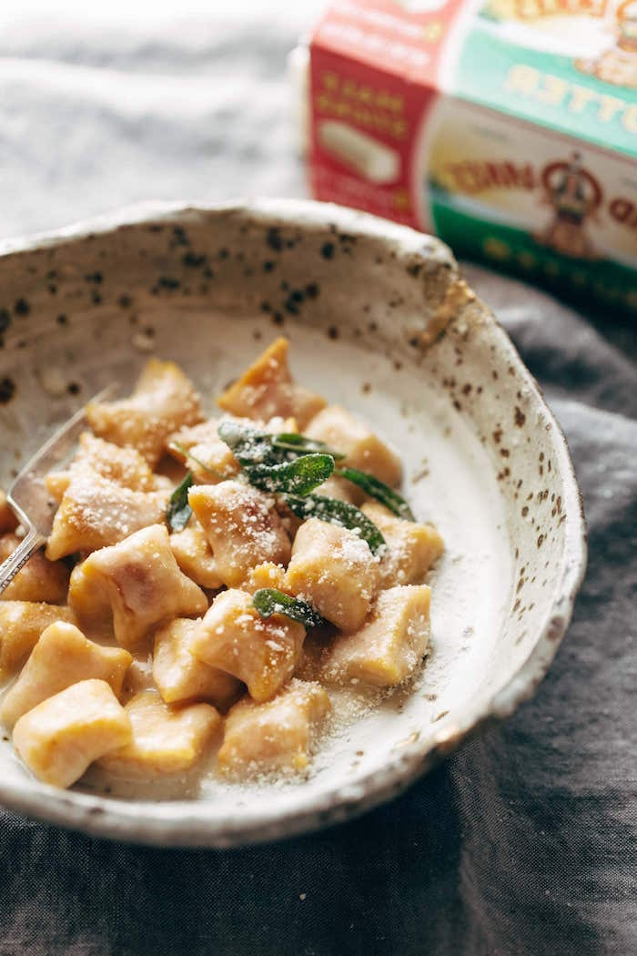 small bowl filled with pumpkin gnocchi with cheesy sauce best gnocchi recipe garnished with fresh mint leaves grated parmesan cheese