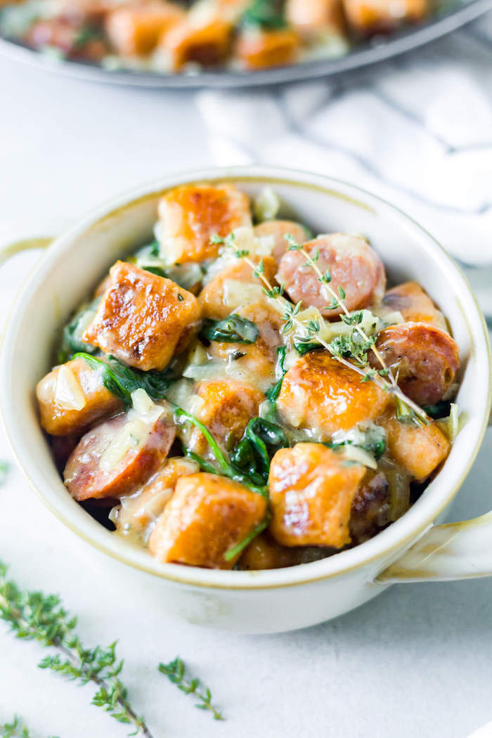 small white bowl filled with baked gnocchi in cheesy sauce with spinach what is gnocchi placed on white surface
