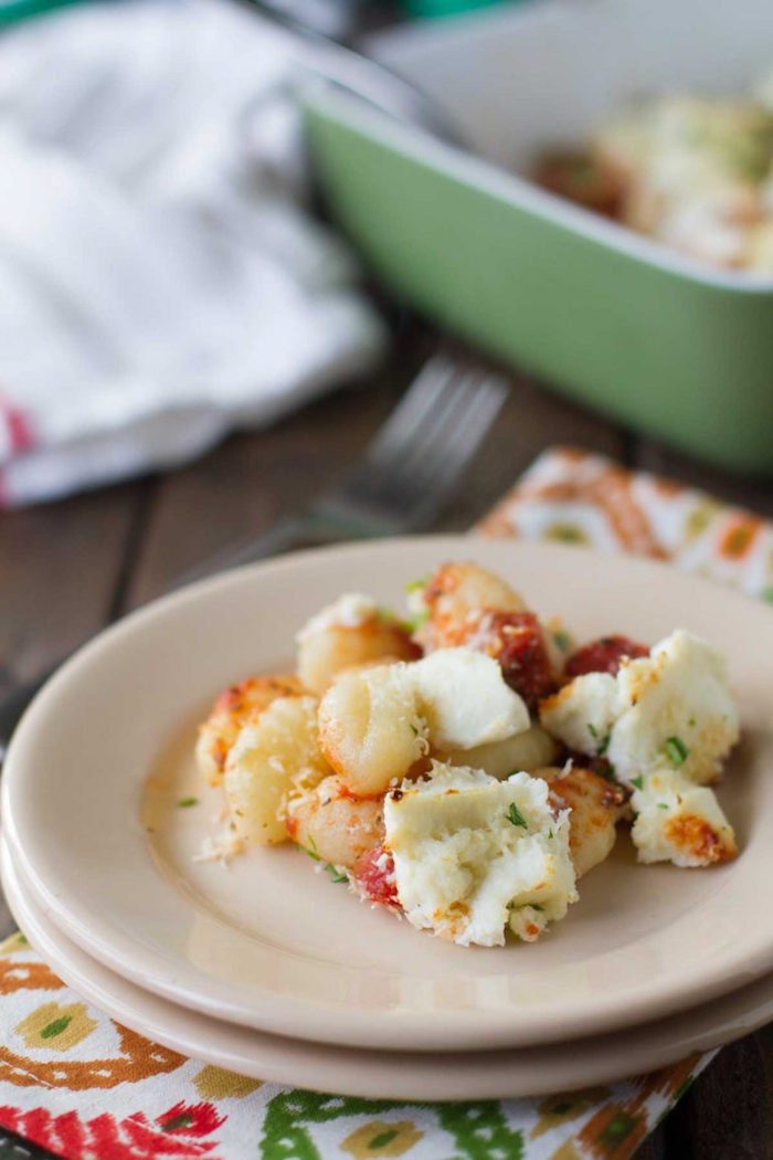 small white plate with baked gnocchi with ricotta cheese best gnocchi recipe colorful napkin under the plate