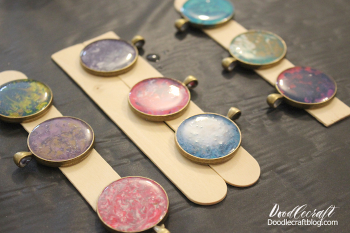 step by step diy tutorial making resin jewelry nine necklace pendants made in different marble colors placed on wooden sticks