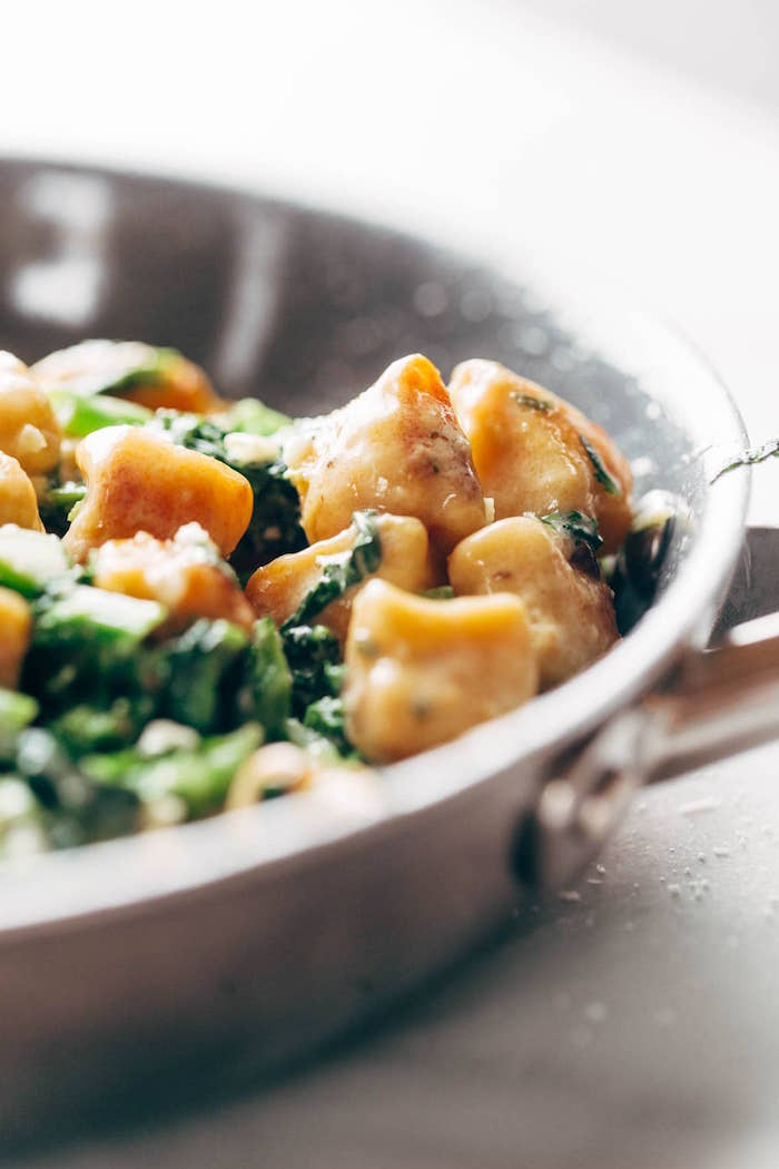 sweet potato gnocchi and kale cooking in metal pan recipes using gnocchi placed on white surface