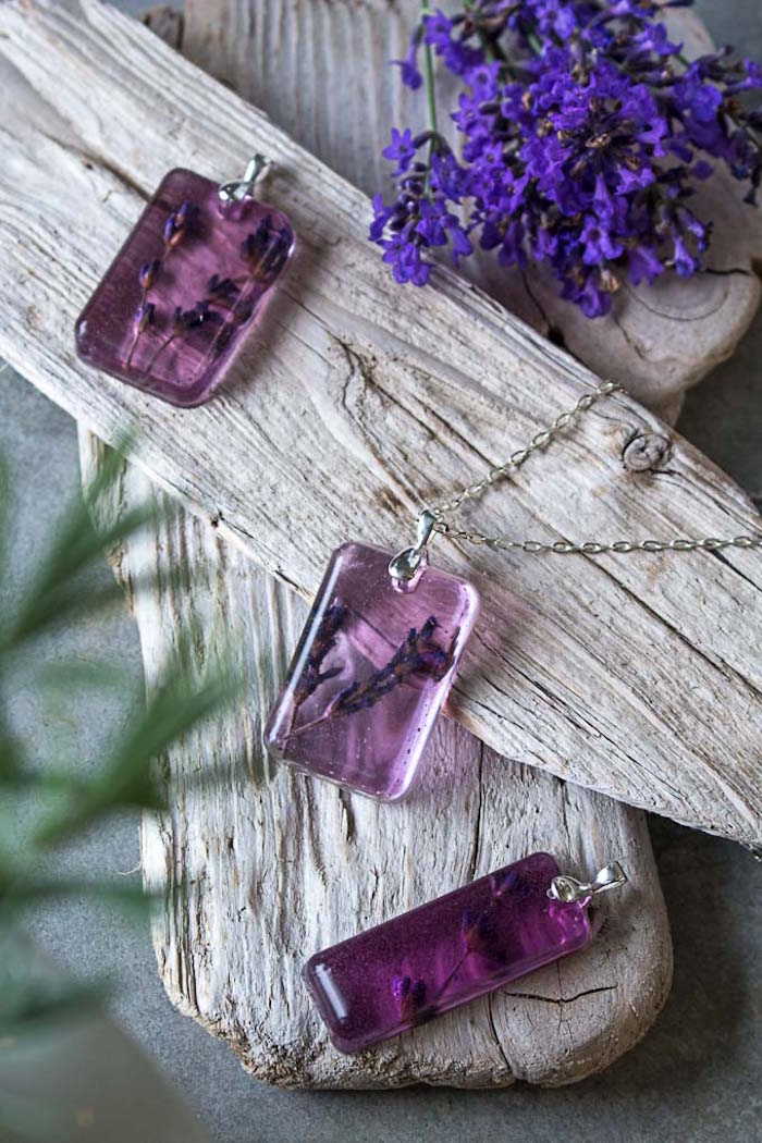 three necklace pendants made with pink resin and dried lavender making resin jewelry arrranged on wooden blocks